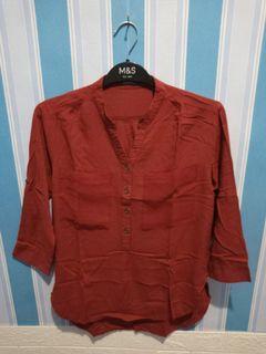 Kemeja merah brand detail