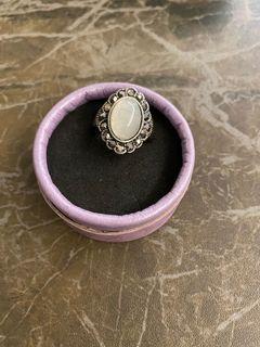 銀色橢圓形戒指!旁邊鑲滿石!中間一粒大型白色石